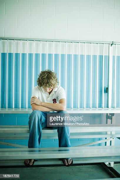 Teenage boy sitting alone on bleachers with head down