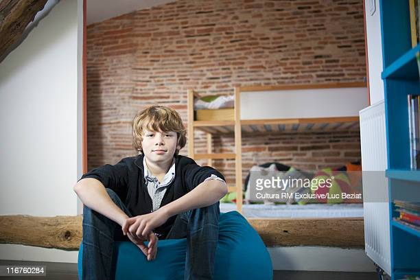 Teenage boy sitting in bedroom