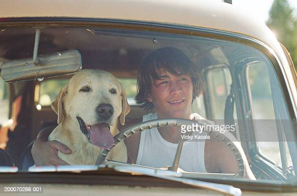 Teenage boy (15-17) sitting in driver's seat of car with dog