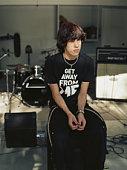 Teenage boy (15-17) sitting on amp in garage