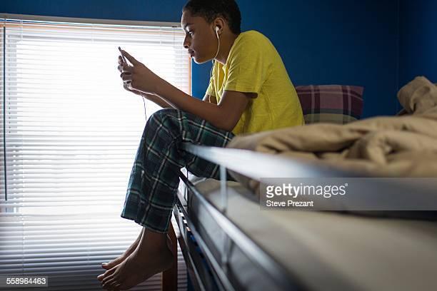 Teenage boy sitting on bunkbed reading smartphone texts