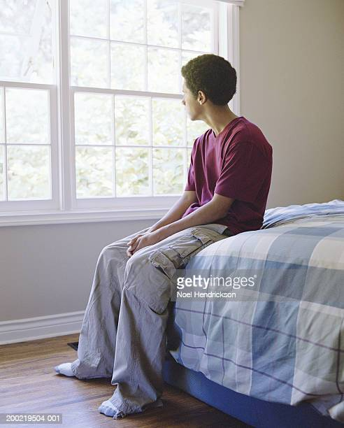 Teenage boy (16-18) sitting on edge of bed, looking out window