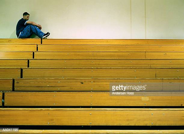 Teenage boy (15-17) sitting on gym bleachers, side view