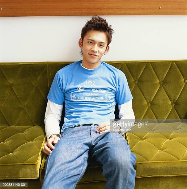 Teenage boy (15-17) sitting on sofa smiling, portrait