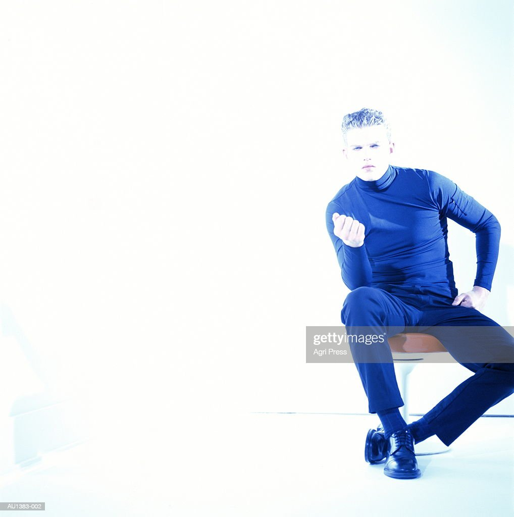 Teenage boy (17-19 years) sitting on stool, portrait (brightly lit) : Stock Photo