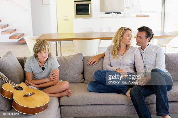 Teenage boy sitting with a guitar on a couch