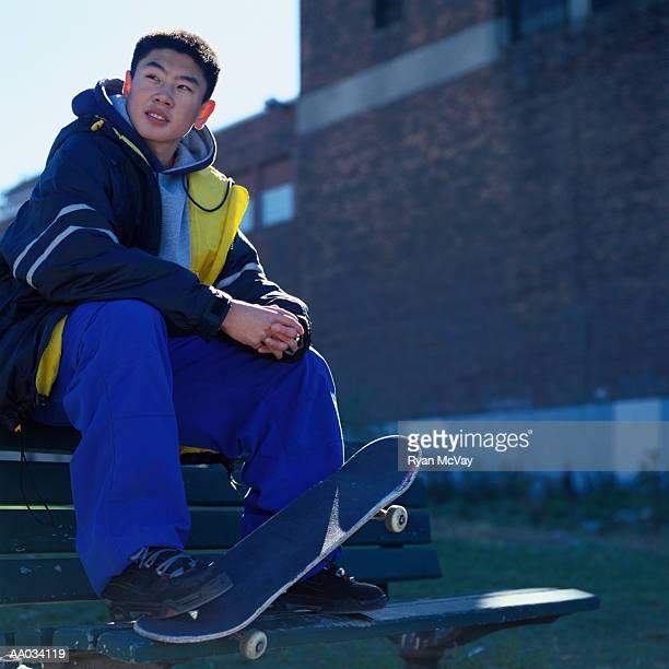 Teenage Boy Sitting With a Skateboard