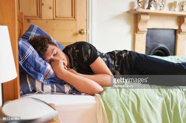 Teenage boy sleeping on his bed