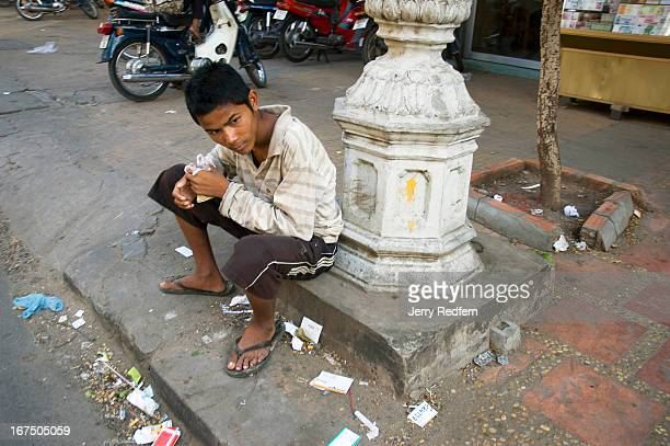 A teenage boy sniffs a bag of glue along a busy street in the middle of the capital Homeless boys around the country often sniff glue for two reasons...