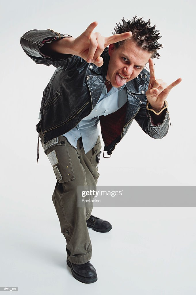teenage boy spiked hair wears leather jacket stands toward camera gesturing sticks out his tongue : Stock Photo