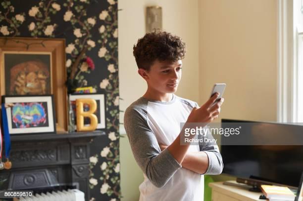 Teenage boy standing in living room texting on smartphone