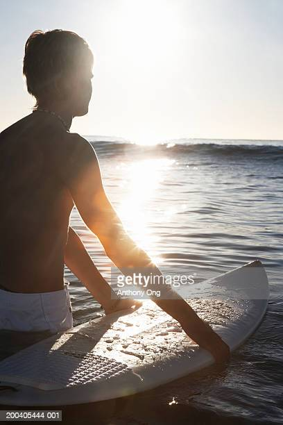 Teenage boy (15-17) standing in sea holding surfboard (sunflare)
