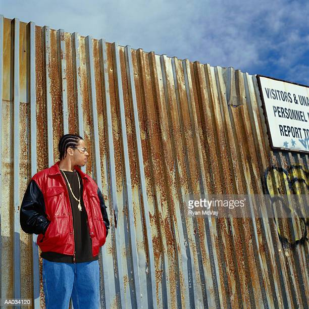 Teenage Boy Standing Near Rusty Fence