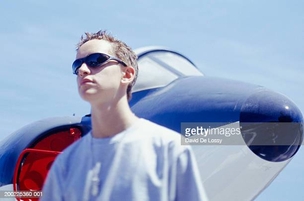 Teenage boy (16-17) standing near small plane