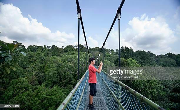 Teenage boy standing on a bridge taking a photo