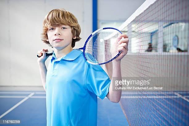 Teenage boy standing on badminton court
