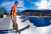 Teenage boy standing with a skateboard on top of a ramp