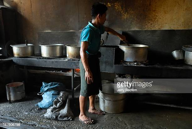 A teenage boy stirs a pot of curry in the kitchen of a teashop in downtown Mandalay There are about 40 boys working in this teashop all from the same...