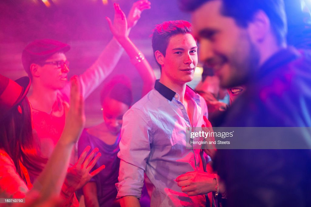 Teenage boy surrounded by group of people dancing at party : Stock Photo