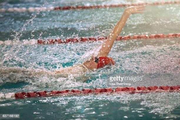 Teenage Boy Swimming Backstroke at a High School Swim Meet