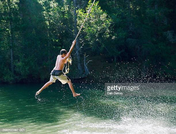 Teenage boy (13-15) swinging on rope over lake, rear view