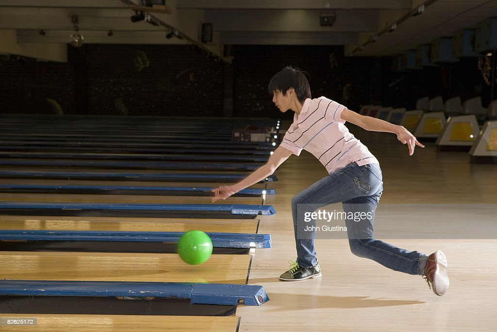 Teenage boy (15-17) throwing a bowling ball