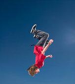 Teenage boy (16-17) upside down in midair