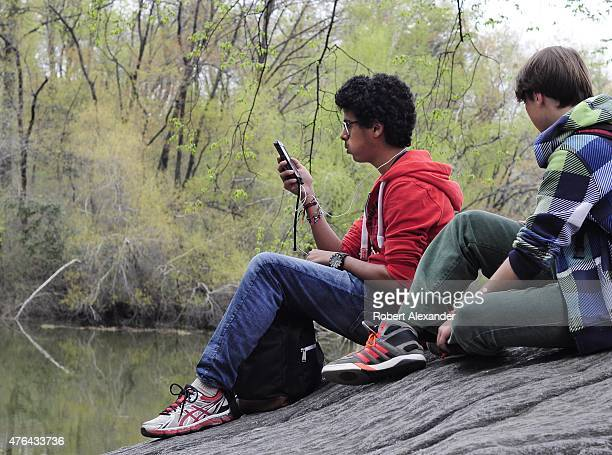 A teenage boy uses his smartphone as he and a friend visit Central Park in New York NY