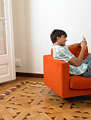 Teenage boy (15-17) using cell phone in living room