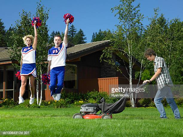 Teenage boy (14-15) using lawnmower, mother and father holding pom poms and jumping