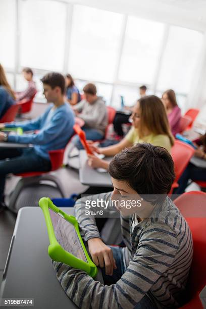 Teenage boy using touchpad during the class at high school.