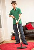 Teenage boy vacuuming