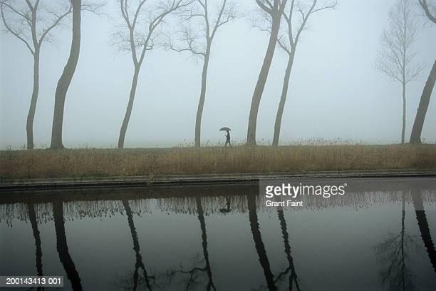 Teenage boy (14-16) walking with umbrella along canal