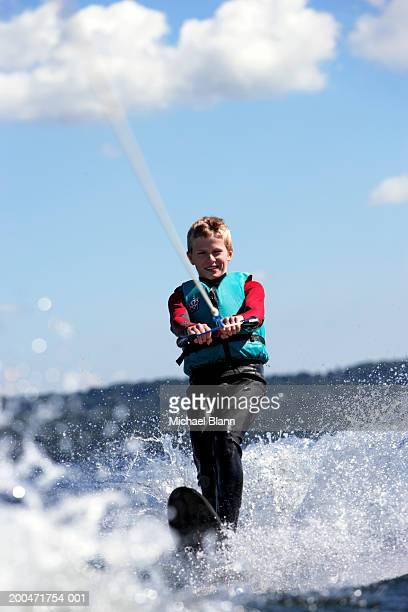 'Teenage boy (13-15) waterskiing, smiling'