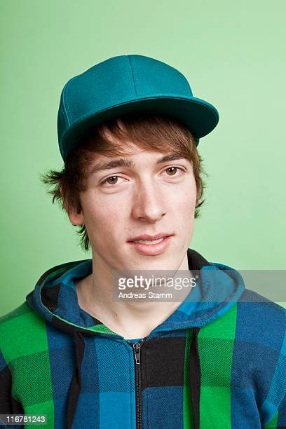 A teenage boy wearing a hoodie and baseball cap, portrait, studio shot