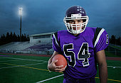 Teenage boy (17-19) wearing football uniform, portrait, night
