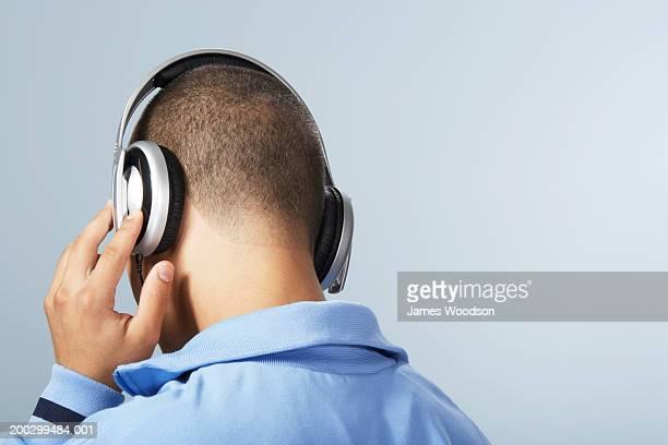 Teenage boy (16-18) wearing headphones, hand to earpiece, rear view