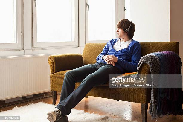 A teenage boy wearing headphones sitting on a couch