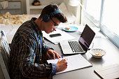Teenage boy wearing headphones works at desk in his bedroom