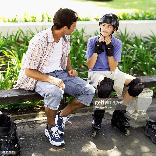 Teenage boy wearing roller blades and sitting on a park bench with his father putting on safety gear