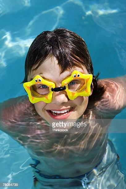 Teenage boy wearing star-shaped goggles in pool