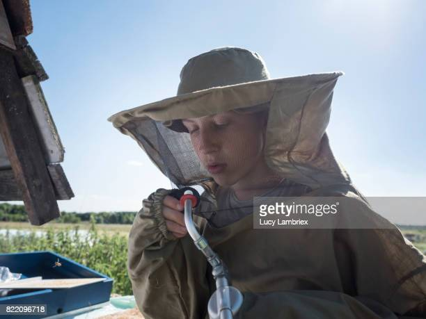 Teenage boy with a bee smoker