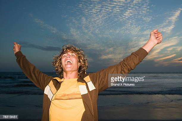 Teenage boy with arms raised by ocean at twilight