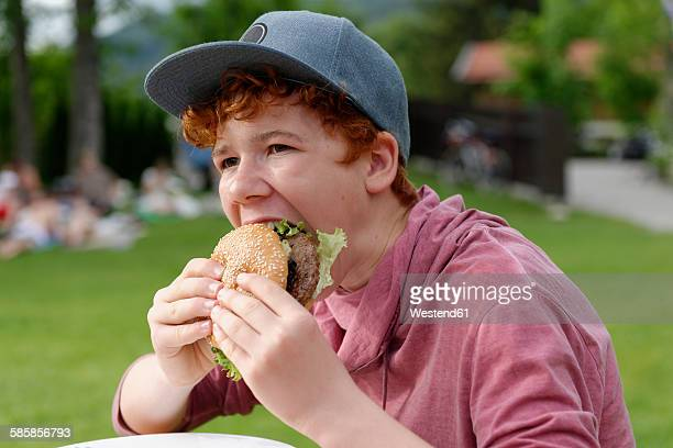 Teenage boy with baseball cap eating hamburger
