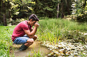 Teenage boy with camera in the lake, taking picture. Summer vacation adventure.