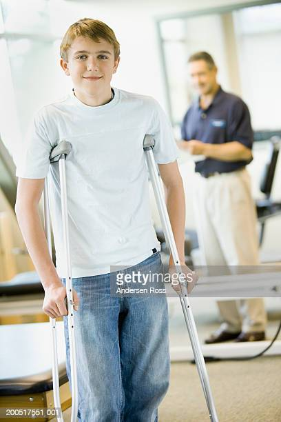 Teenage boy (14-16) with crutches, physical therapist in background