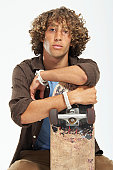 Teenage boy (16-18) with curly hair, leaning on skateboard, portrait