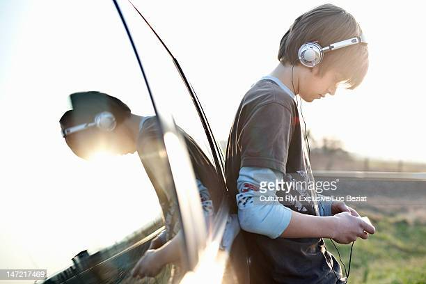 Teenage boy with headphones by car