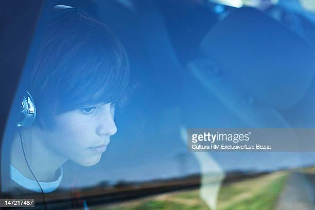 Teenage boy with headphones in car