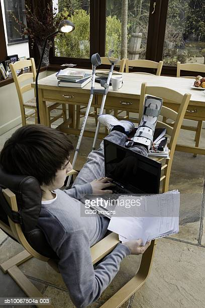 Teenage boy (16-17 years) with leg in cast up on chair using laptop
